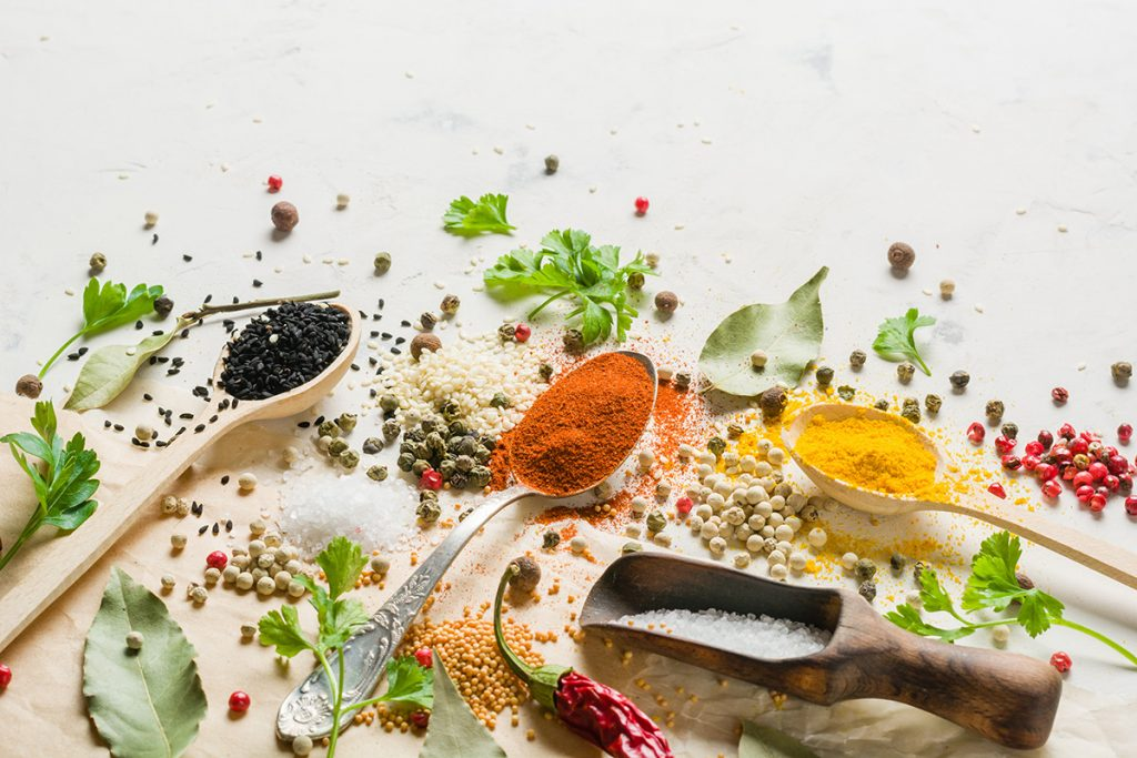 Spices in different spoons on a stone white background. A scattering of seasonings and spices.